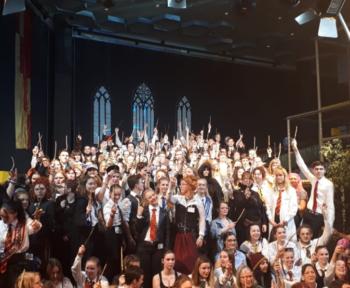 Mehrere Menschen stehen in Harry-Potter-Kostümen in einer Reihe auf einem Potest im Zauberschloss