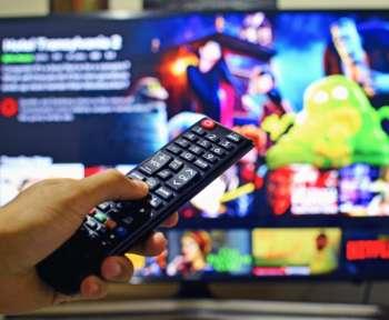 Eine Fernbedienung wird vor einen Fernseher gehalten, auf dem Netflix läuft