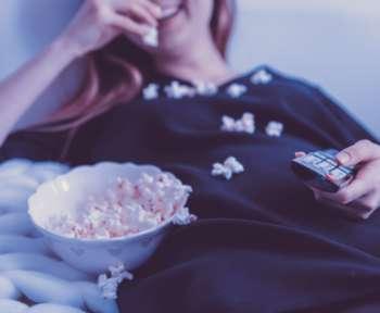 Eine junge Frau liegt auf dem Bett und konsumiert Popkorn. Dabei fällt fiel Popkorn daneben und ist auf ihr verteilt. Offensichtlich schaut sie fern.