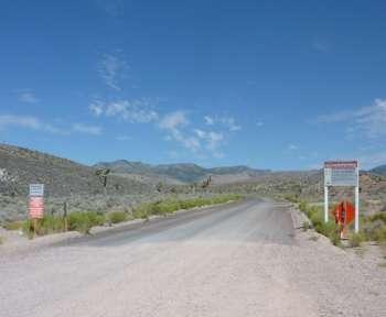 Eine Wüstenstraße mit Warnschildern, die ein militärisches Sperrgebiet ankündigen.