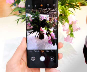 Das Huawei P30 mit geöffneter Kamera wird vor eine Blumenvase gehalten
