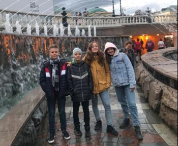 Zwei Jungen und zwei Mädchen posieren vor einem Brunnen in Moskau