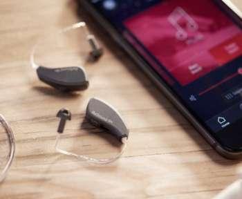 Ein Smartphone mit geöffnetem Musikplayer und zwei Hörgeräte liegen nebeneinander auf einem Tisch
