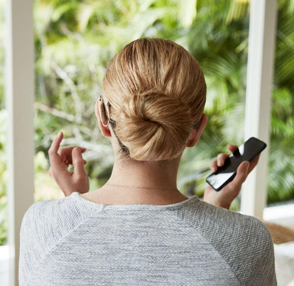 Eine Frau mit einem Hörgerät im Ohr und einem Smartphone in der Hand sitzt auf einem Sofa