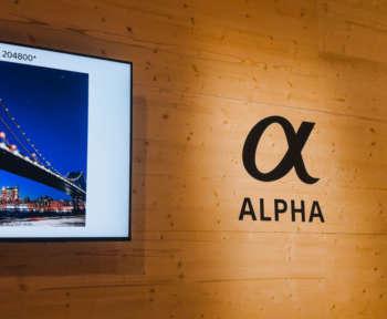 """Ein Sonyfernseher hängt an einer Wand neben dem Wort """"ALPHA""""."""