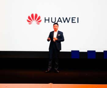 Ein Mann steht vor einer Leinwand mit dem Huawei-Logo.