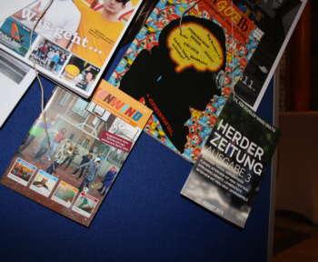 Mehrere Schüler*innenzeitungen hängen an einer Pinwand, darunter auch die Herderzeitung