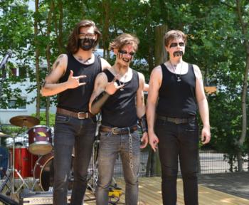 Herders Heavy-Metal-Band steht auf einer Bühne in Kostümen und mit Musikinstrumenten