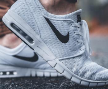 Zwei Füße, die Sneaker der Marke Nike tragen stehen auf dem Fußboden