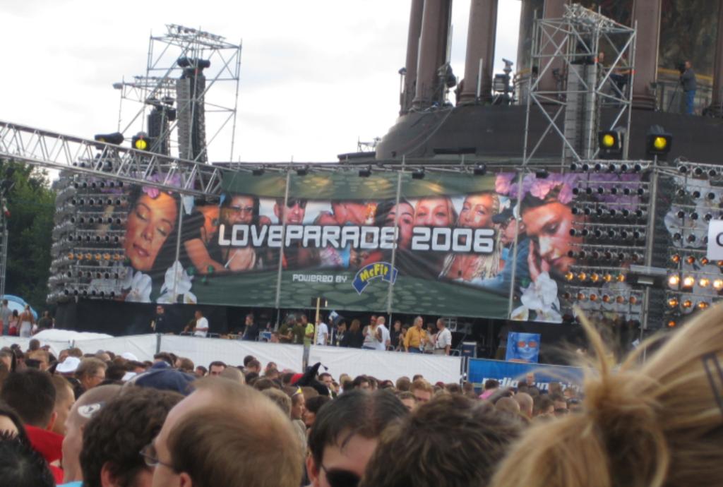 """Hinter einer Menschenmenge leuchtet die Aufschrift """"Loveparade 2006"""" auf einem Display"""