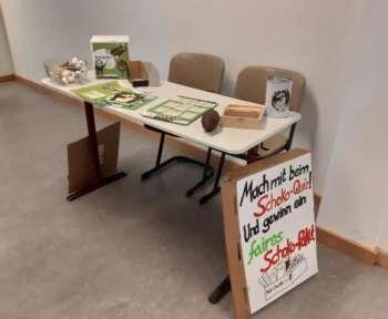 Im Schulflur ist ein Stand aufgebaut. Schilder informieren über Umweltschutz und den Klimawandel.
