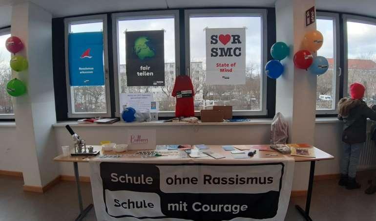 """Im Schulflur ist ein Stand aufgebaut. Auf dem Schild daneben ist das Logo von """"Schule ohne Rassismus - Schule mit Courage"""" zu sehen"""