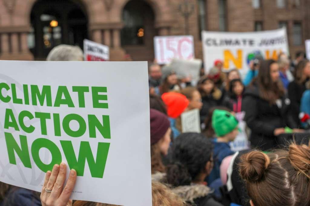 """Demonstrant*innen von Fraidays for Future halten Schilder in die Luft. Auf einem im Vordergrund steht """"Climate Action Now""""."""