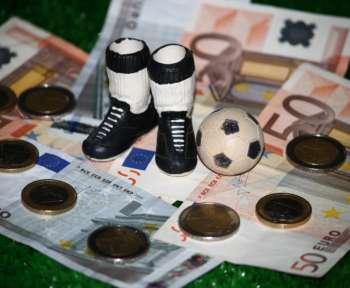 Ein Symbolbild. Die Miniaturmodelle von Schuhen und einem Fußball liegen auf Geldscheinen.