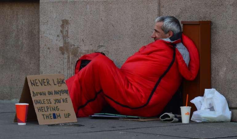 Ein Obdachloser in einem Schlafsack liegt gegen eine Wand gelehnt auf der Straße.