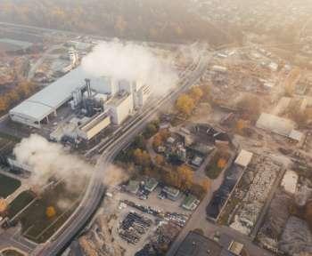Aus einem Kraftwerk steigt Rauch auf. Eine Ansicht aus der Vogelperspektive über eine Stadt.
