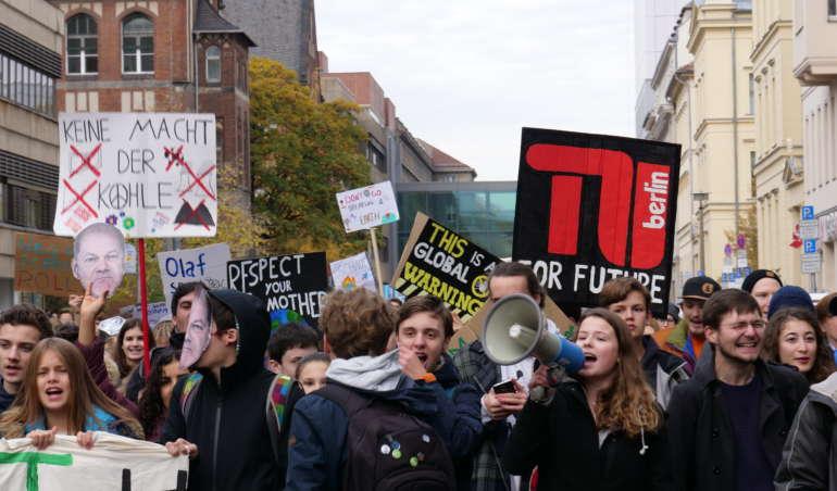 Luisa Neubauer steht in einer Gruppe Demonstrant*innen mit einem Megaphon