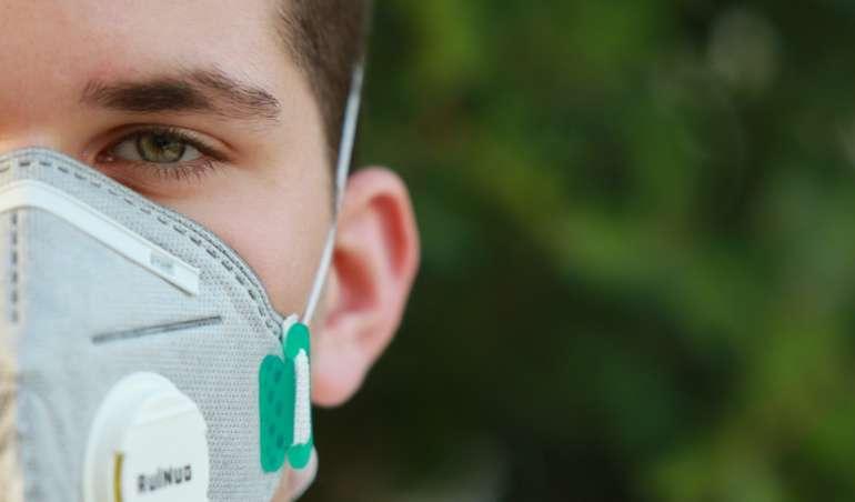 Ein junger Erwachsener schützt sich mit einer Atemmaske