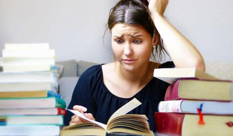 Ein Mädchen schaut genervt in ein Schulbuch. In etwa so stellt man sich Unterricht während der Sommerferien vor.