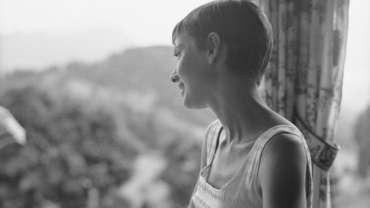 Audrey Hepburn sitzt in einer Rolle am Fenster eines Zuges