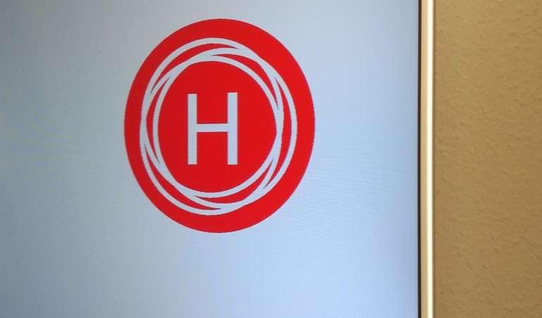 Ein Fernseher steht in einem Schrank. Er zeigt das Logo der Herderzeitung auf weißem Hintergrund.