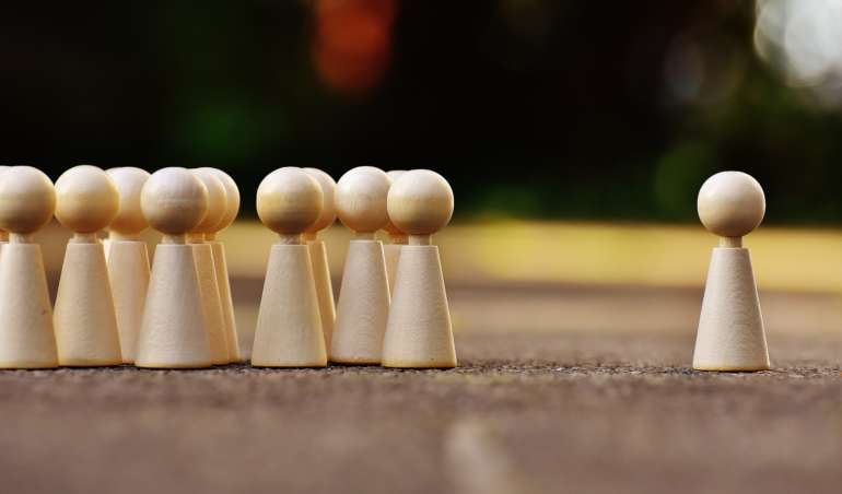Symbolbild: Eine Spielfigur steht abgewandt von allen anderen
