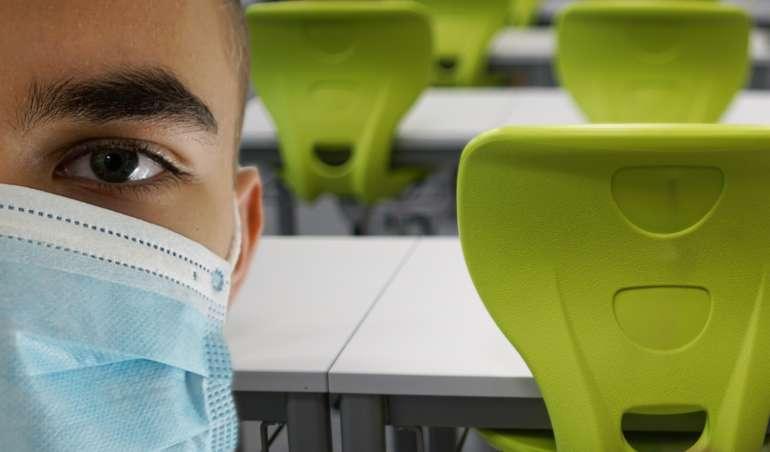 Schüler mit Maske steht in einem Klassenraum