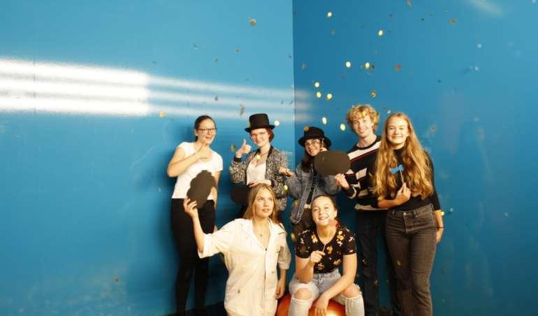 Redaktion der Herderzeitung steht vor einer blauen Wand. Konfetti fällt vom Himmel.