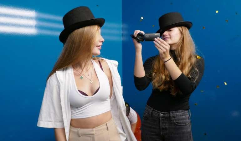 Lilly und Ronja stehen vor einer blauen Wand und filmen sich gegenseitig.