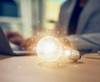 Symbolbild für Innovation und Digitalisierung. Glühbirne liegt vor einem Laptop.