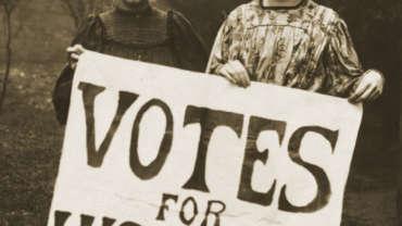 """Zwei Frauen mit einem Schild """"Votes For Women"""""""