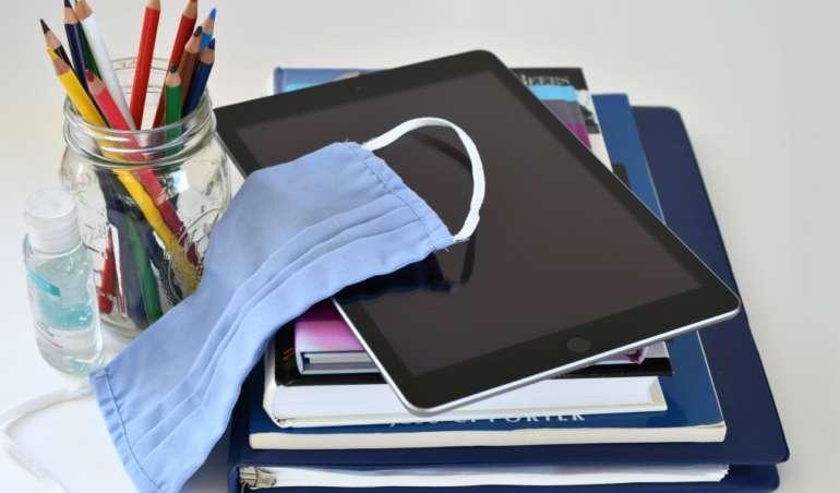 Maske, Tablet, Stifte und Schulbücher: Symbolbild fürs Homeschooling