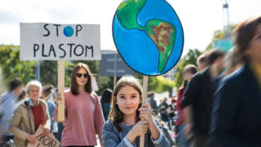 """Klimastreik. Ein Mädchen hält ein Schild mit der Erde, dahinter ein Frau eines mit der Aufschrift """"Stop Plastom"""""""