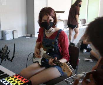 Schülerin spielt die Gitarre während einer Aufzeichnung