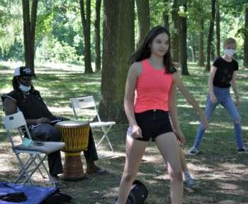 Schüler*innen tanzen. Im Hintergrund sitzt der Dozent mit einer Trommel.