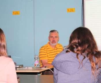 Jan Feddersen erzählt. Im Vordergrund sitzen zwei Schülerinnen.