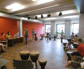 Schüler*innen spielen auf Afrotrommeln