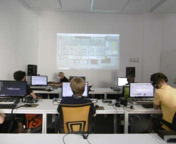 Schüler*innen sitzen an einem Tisch und schneiden Tonschnipsel am Computer